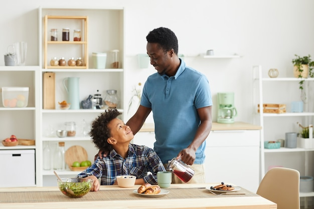African family of two father and son having breakfast together in domestic kitchen