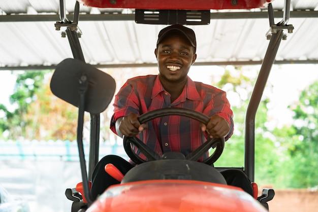 Африканский фермер управляя трактором в ферме во время сбора в сельской местности. концепция сельского хозяйства или выращивания