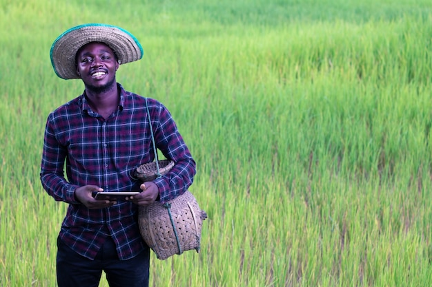 African farmer is happily working on his farm with using tablet.agriculture or cultivation concept