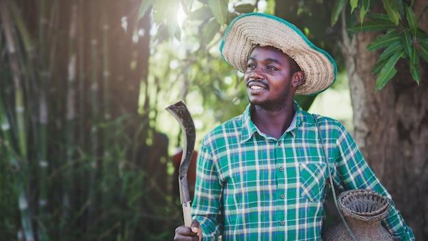 Африканский фермер счастливо работает на своей ферме. сельское хозяйство или концепция выращивания