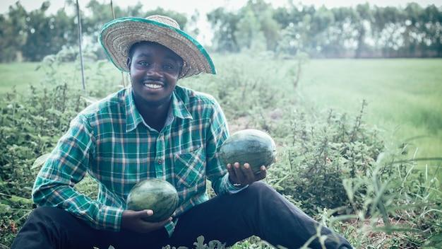 アフリカの農民は彼の農場で楽しく働いています。農業または栽培の概念