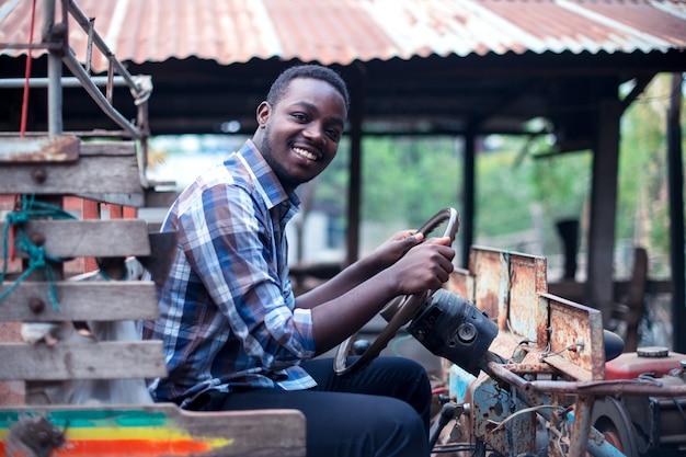 アフリカの農夫の男が田舎で小さなトラクターを運転する