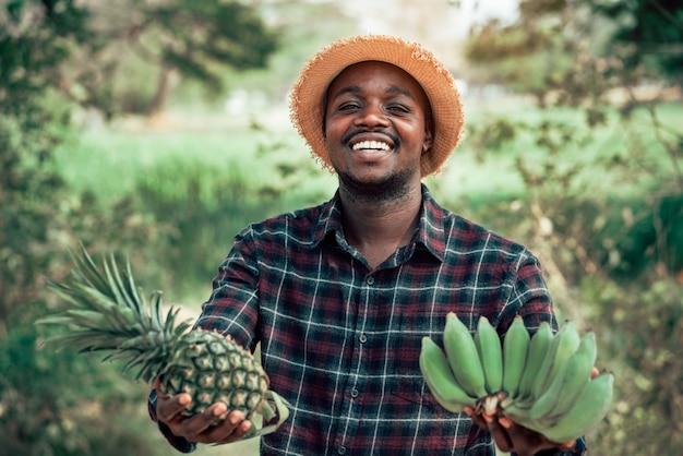 Африканский человек фермера держа ананас и банан на органической ферме с улыбкой и счастливым. концепция земледелия или культивирования
