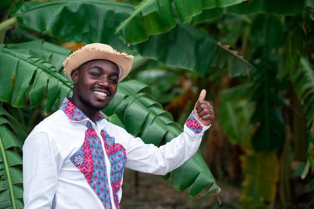 Африканский фермер человек, стоящий с банановым деревом на органической ферме.