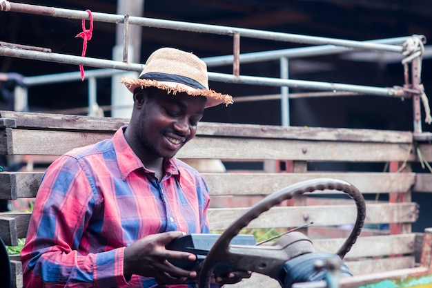 African farmer man with retro radio broadcast receiver on shoulder stands happy smiling outdoor on old car with background