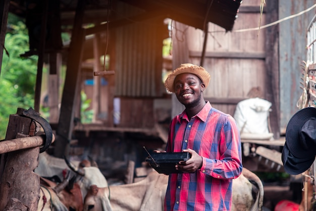 African farmer man with retro radio broadcast receiver on shoulder stands happy smiling outdoor on old cow stall background