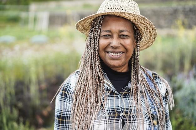 수확 기간 동안 카메라에 미소 아프리카 농부-얼굴에 초점