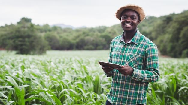 アフリカの農夫はタブレットを持って緑の農場に立っています。16:9スタイル