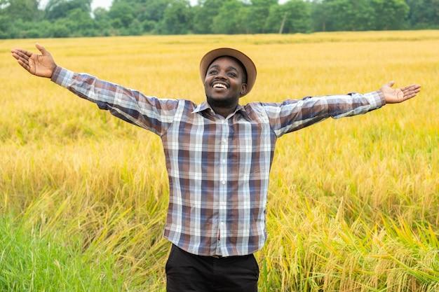 미소와 행복으로 유기농 쌀 필드에 서있는 아프리카 농부. 농업 또는 재배 개념