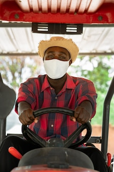 African farmer wear face mask and driving tractor in farm during harvest in countryside. agriculture or cultivation concept