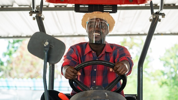 African farmer wear  face shield and driving tractor in farm during harvest in countryside. agriculture or cultivation concept