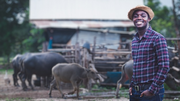 African farmer with hat stand in the water buffalo farm.agriculture or cultivation concept