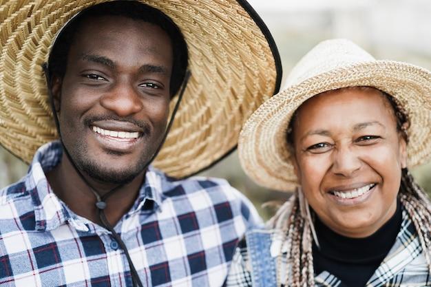 収穫期にカメラに微笑むアフリカの農民-男の顔に焦点を当てる