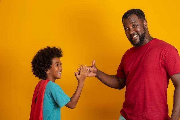 アフリカの父と息子が昼間にスーパーヒーローを演奏します。楽しい黄色の壁を持つ人々。フレンドリーな家族の概念。