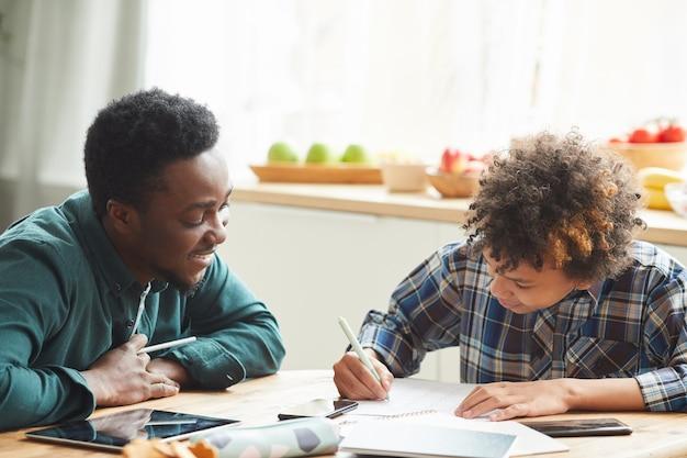 소년 노트북에 메모를 만드는 동안 자료를 설명하는 집에서 온라인 교육 중에 공부하는 아들을 돕는 아프리카 아버지