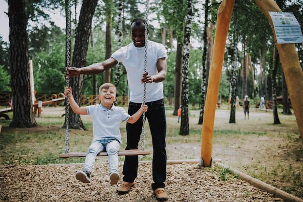 African father swinging son adopted child laughs