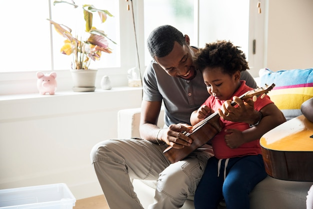 African father teaching son how to play guitar