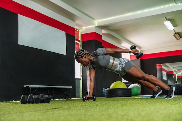 ジムでケトルベルを使って上腕三頭筋の調子を整えるエクササイズをしているアフリカの女性ボディービルダーアスリート。ジムでスポーツウェアとクロスフィットトレーニングルーチンを行うアフリカの女性のボディービルダー