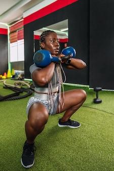 ジムでケトルベルを使って上腕二頭筋と肩の調子を整えるエクササイズをしているアフリカの女性ボディービルダーアスリート。ジムでスポーツウェアとクロスフィットトレーニングルーチンを行うアフリカの女性のボディービルダー