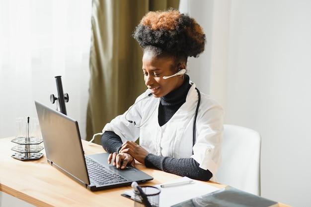 Африканская женщина-врач консультирует пациента и делает видеозвонок с веб-камеры на ноутбуке.