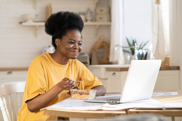 African female eat and watch video or webinar on laptop or make conference call to friends on break