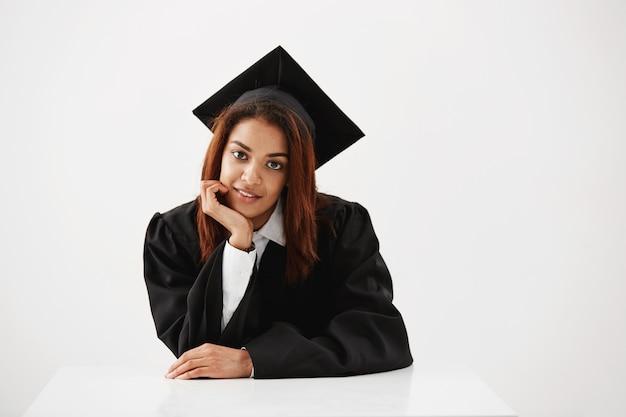 Африканский женский выпускник улыбается сидя.