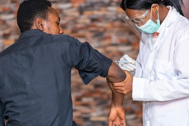 若い黒人男性に予防接種をするアフリカの女性医療関係者