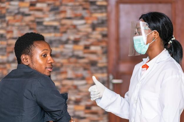 フェイスマスクと盾を身に着けているアフリカの女性医療関係者は若い黒人男性に親指を与える
