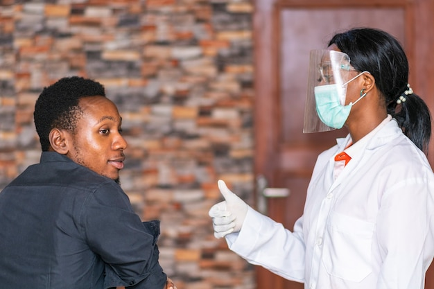 African female medical personnel wearing face mask and shield gives a thumbs up to a young black man
