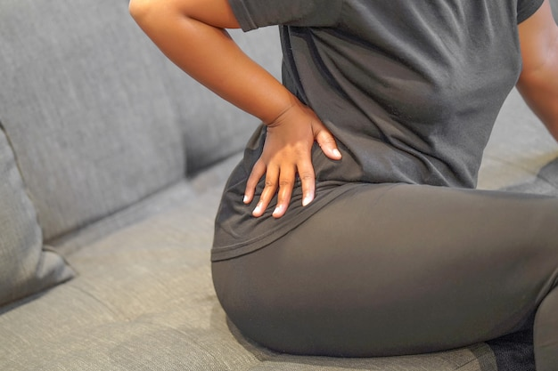 African female pain at lower back.