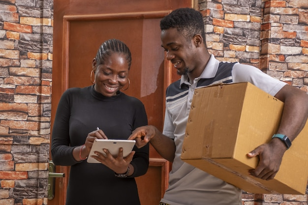 African female signing a proof of delivery while receiving a parcel from the courier