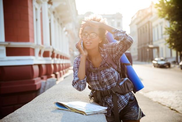 Африканский женский путешественник с рюкзаком, говоря на телефоне на улице.