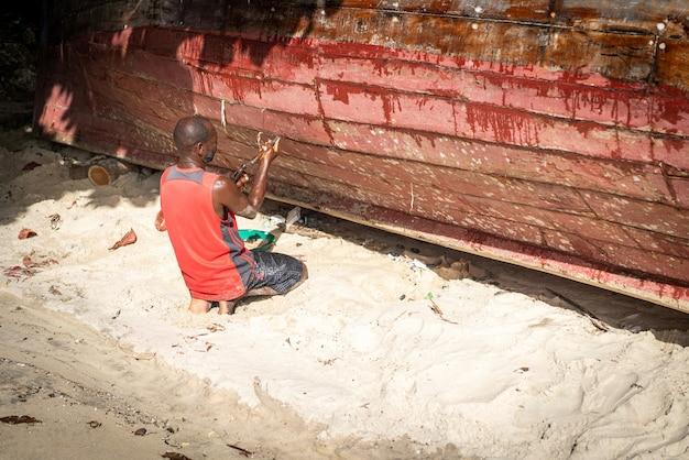 彼のボートを修理するビーチでアフリカの漁師