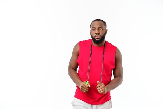 Африканская фитнес-модель со скакалкой на сером фоне. красивый мускулистый мужчина позирует с прыжками через скакалку.