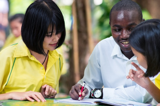 African foreign teacher teaching uniform asian student