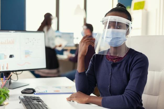 Covid19に対する職場での安全予防策としてフェイスマスクを着用しているアフリカのフリーランスの女性。世界的大流行の際の社会的距離を尊重する金融会社で働く多民族のビジネスチーム。