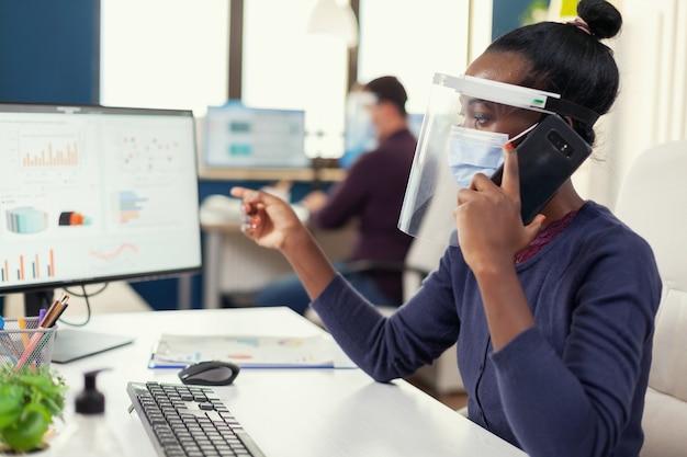 コロナウイルスの間にフェイスマスクを身に着けている財務グラフについてスマートフォンで議論しているアフリカのフリーランサー
