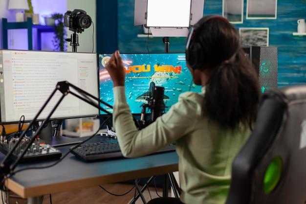 경쟁에서 승리한 후 멀티플레이어와 함께 승리를 축하하는 아프리카 게임 스트리머. 네온 불빛으로 집에서 비디오 게임 토너먼트 동안 온라인 스트리밍 사이버 공연.
