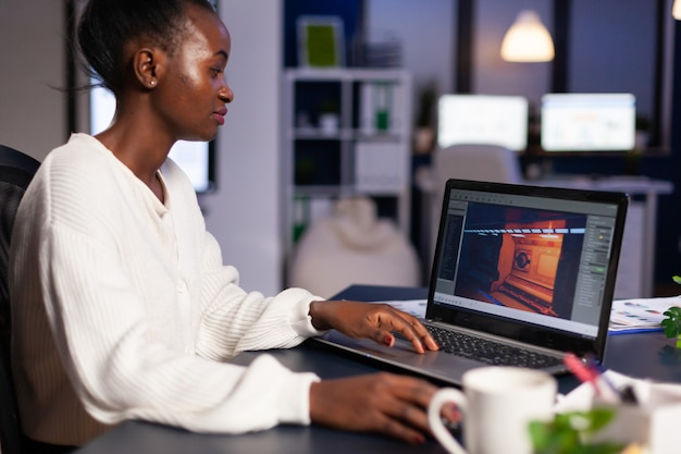 African gamer creator testing game over level interface, developing new design in midnight from business office using laptop