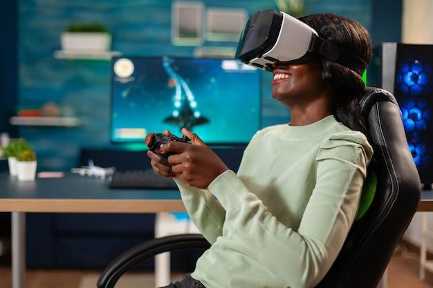 E-sport di giocatori africani con vr seduto su una sedia utilizzando il controller wireless. campionato di videogiochi sparatutto spaziale virtuale nel cyberspazio, giocatore di esport che si esibisce su pc durante il torneo di gioco.