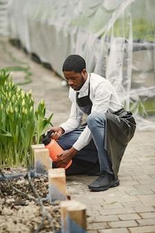 Ragazzo giardiniere africano. giardiniere con un annaffiatoio. aiuole.