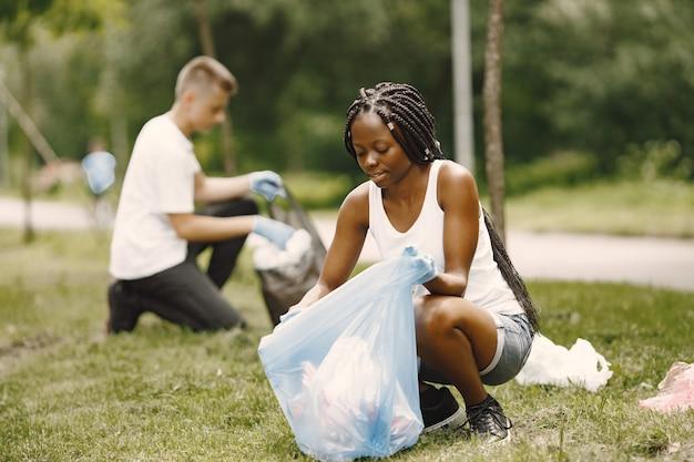 アフリカの女の子とヨーロッパの男の子がゴミを拾っています。公園を横向きに片付ける活動家。