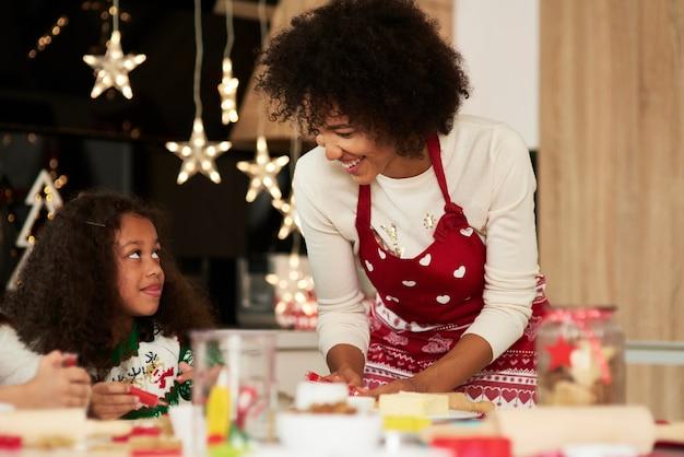 彼女のお母さんの助けを借りてクッキーを焼くアフリカの女の子