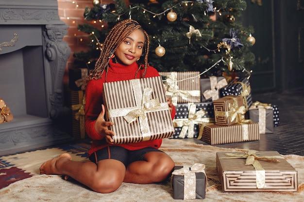 Ragazza africana in un addobbo natalizio / donna in un maglione rosso. anno nuovo concetto.
