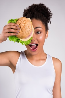 African girl closes her mouth and hides behind a hamburger.