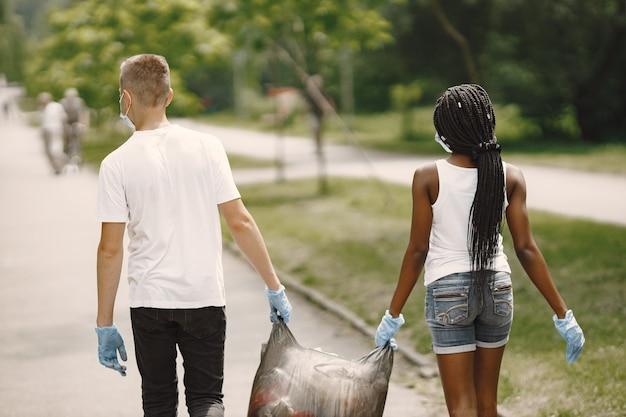 Ragazza africana e ragazzo europeo che indossano maschere e guanti. hanno ripulito il parco dalla spazzatura e portano insieme la borsa.