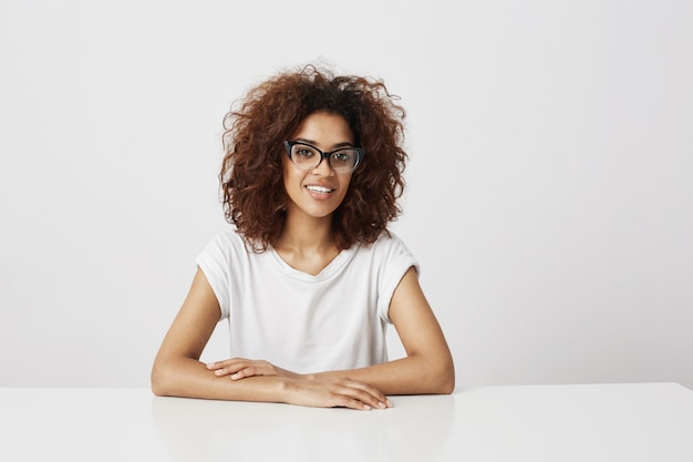 African girl in glasses  sitting over white wall. copy space.