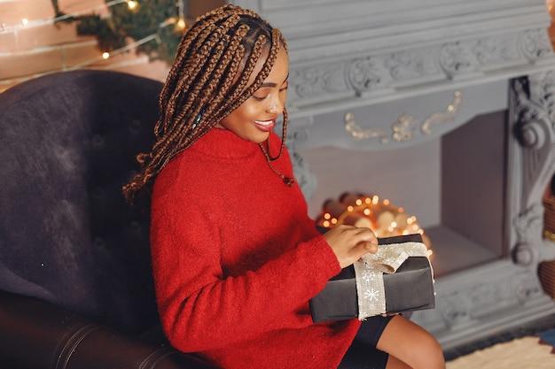 クリスマスの飾り付けのアフリカの女の子/赤いセーターの女性。新年のコンセプト。
