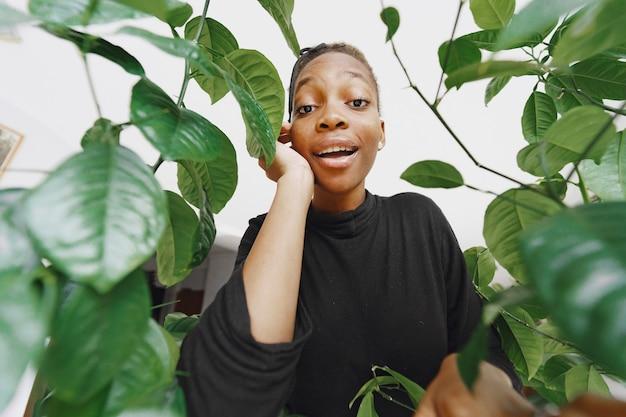 部屋のアフリカの女の子。植物の近くのスタイリッシュな女の子。黒のセーターを着た女性。