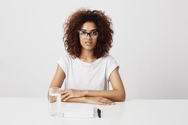 白い壁に座っているガラスのアフリカの女の子。コピースペース。